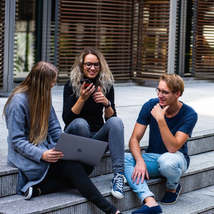 three people sitting on steps outside of a building laughing with a laptop