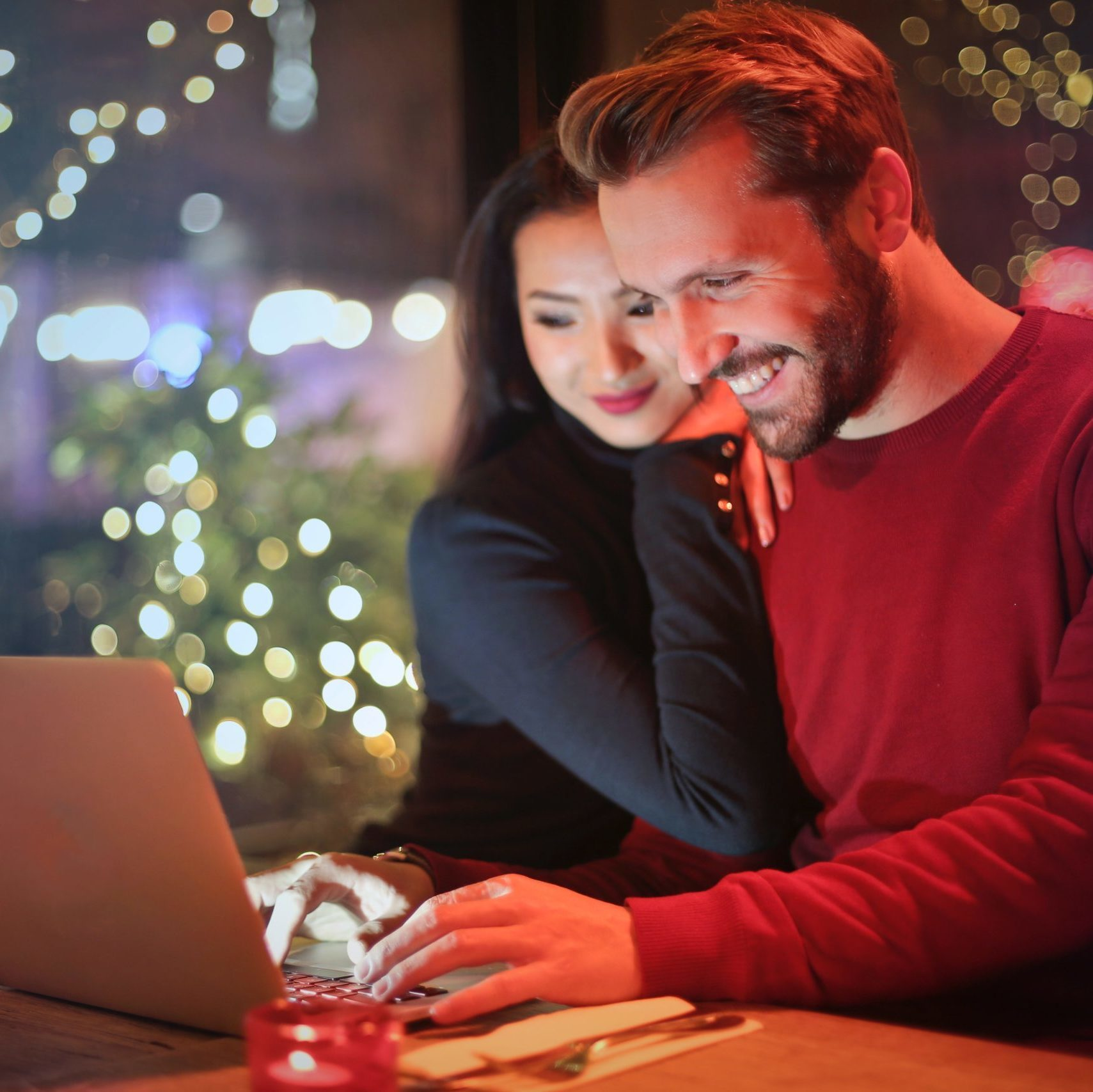 couple smiling at laptop with lights in background